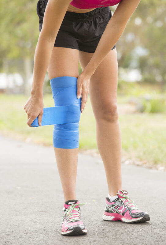 Female athlete wrapping her knee with a cooling bandage