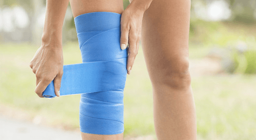 Female athlete with a knee sprain wrapping her knee with a compression bandage